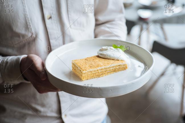 Serer carrying dessert dish in restaurant