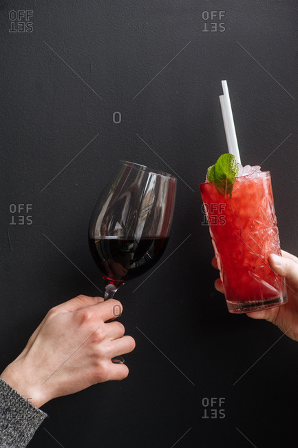 Two people toasting with wine and a cocktail