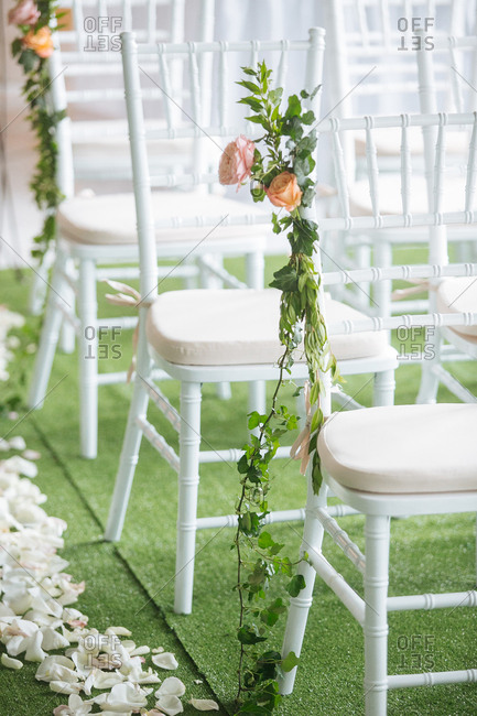White chairs at a wedding reception decorated with roses