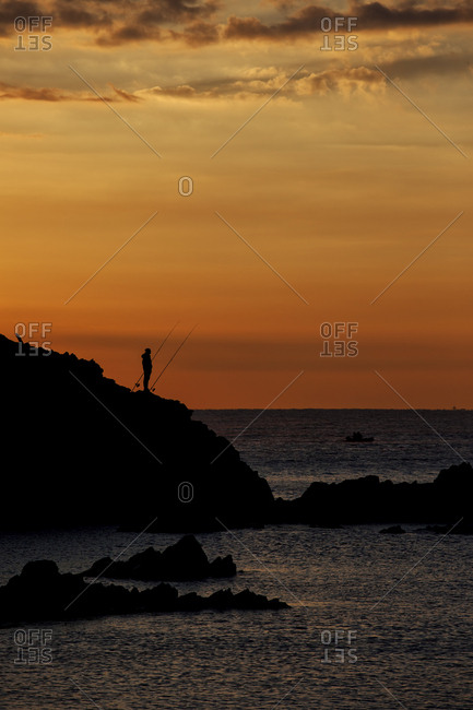 Spain- Costa Brava- Blanes- lone angler and Sa Palomera rock silhouette at sunrise by the Mediterranean Sea