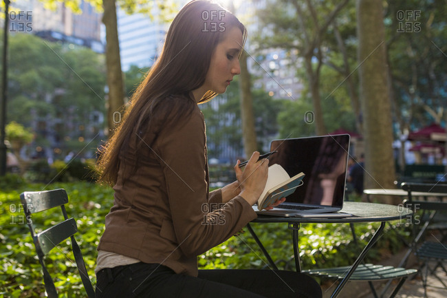 USA- New York- Manhattan- young businesswoman with laptop and notebook sitting at table in a park