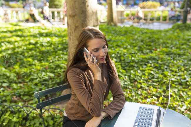 Young businesswoman on the phone sitting at table in a park with laptop