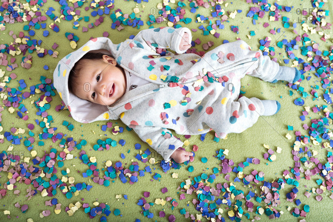 Happy baby girl surrounded by confetti