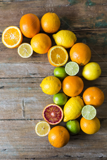 Sliced and whole lemons- oranges and limes on wood