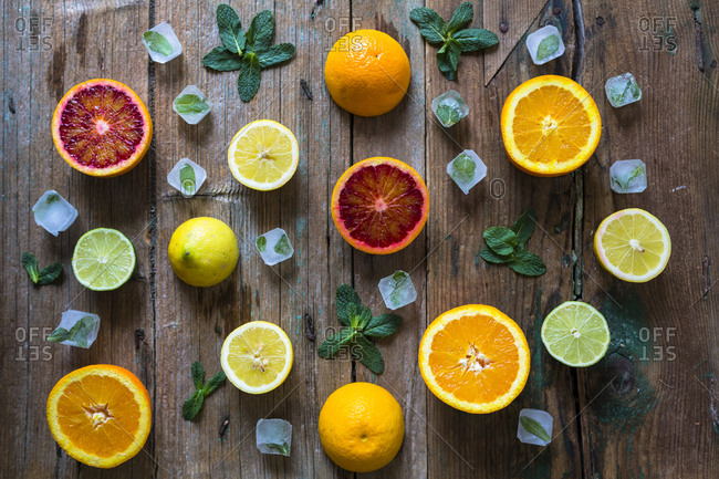 Sliced and whole lemons- oranges and limes- mint leaves and ice cubes on wood