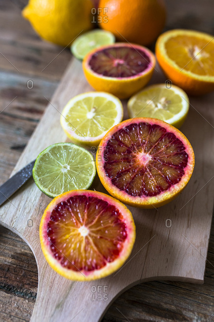 Sliced lemon- oranges and lime on wooden board