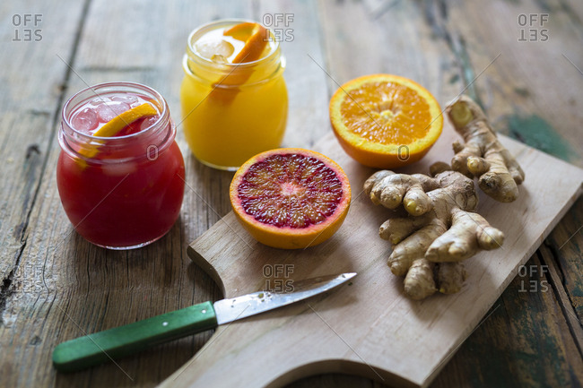 Two glasses of different orange juices- halves of oranges and ginger