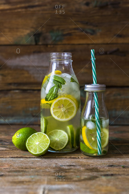 Glass bottles of infused water with lemon- lime- mint leaves and ice cubes