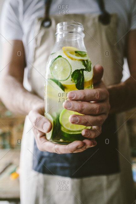Man's hands holding glass bottle of infused water with lemon- lime- mint leaves and ice cubes