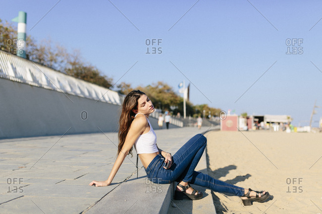 Young woman relaxing on beach promenade at sunset