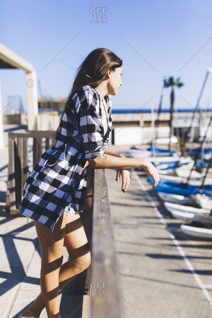 Young pretty woman wearing beach wear standing at balustrade at the harbor