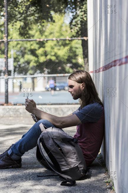 Man sitting down looking at tablet
