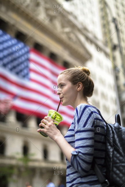 USA- New York City- woman drinking a smoothie in front of New York Stock Exchange