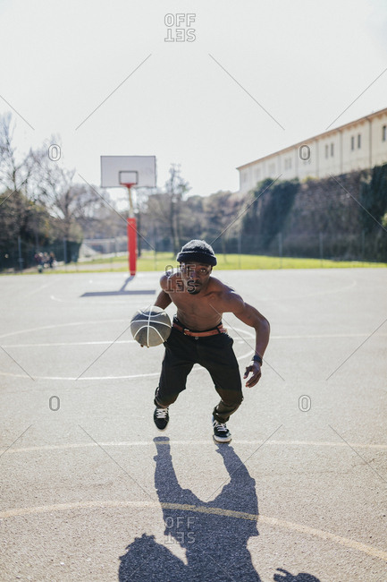 Bare-chested basketball player in action on court
