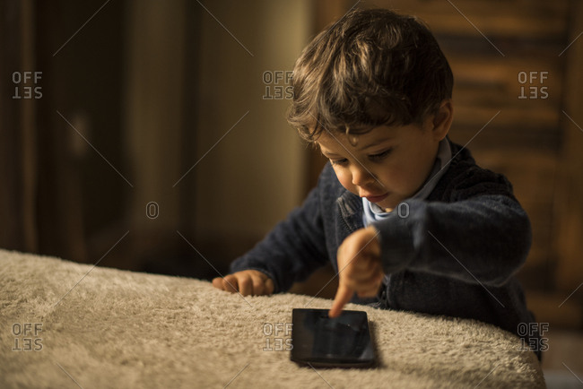 Toddler playing with smartphone at home