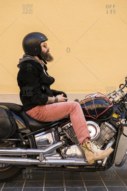 Bearded biker wearing helmet and sunglasses sitting on his motorcycle