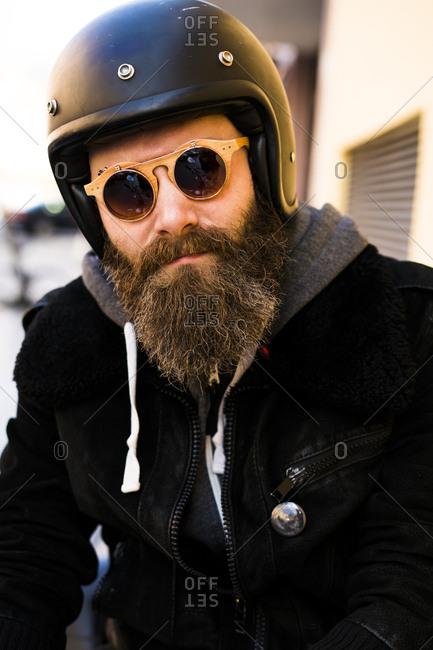 Portrait of bearded biker wearing helmet and sunglasses