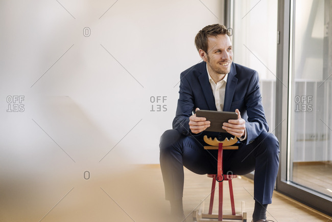 Smiling businessman sitting on rocking horse with tablet