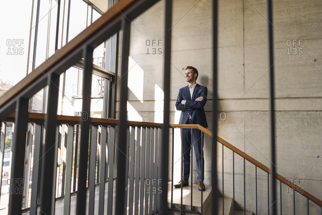 Smiling businessman standing in staircase