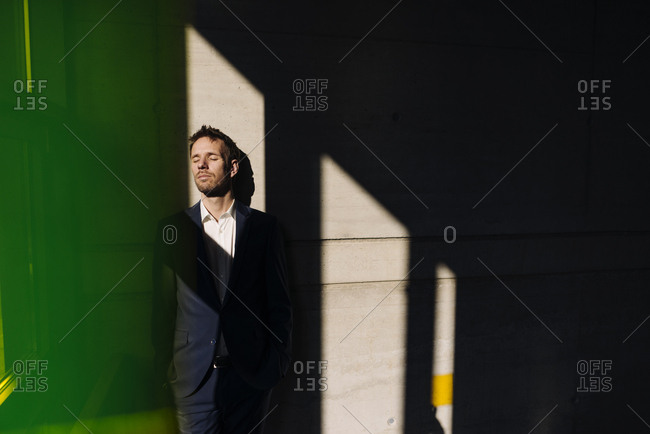 Businessman with closed eyes leaning against a concrete wall