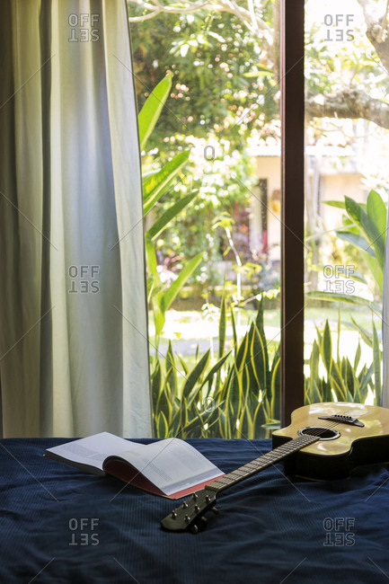Guitar and book on bed. making the bed stock photos   OFFSET