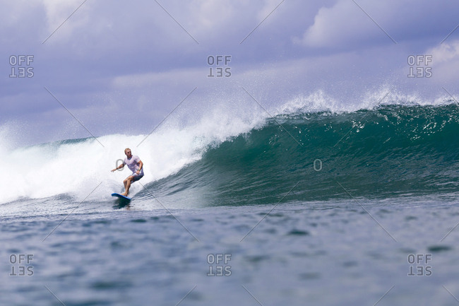 Indonesia- Bali- man surfing on a wave