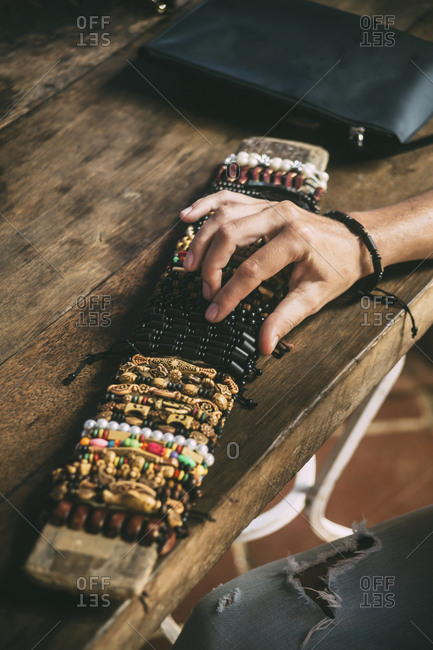 Indonesia- woman choosing from assortment of bracelets