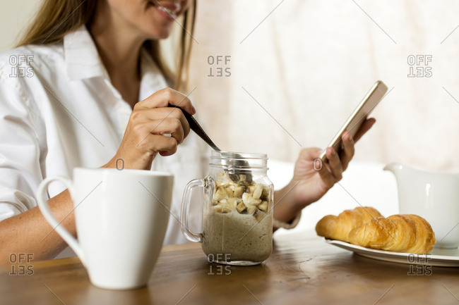 Woman at breakfast table using cell phone