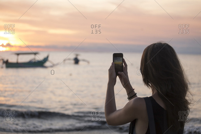 Indonesia- Bali- woman taking a picture of the sunset over the ocean