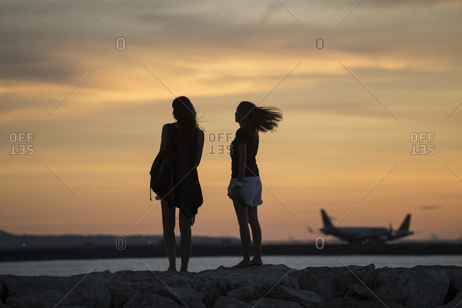 Indonesia- Bali- two women watching the sunset over the ocean