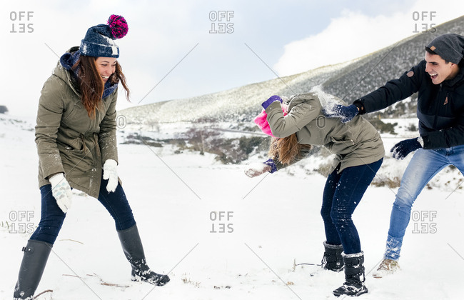 Friends having a snowball fight in the snow