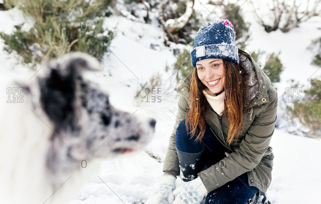 Beautiful woman playing with her dog in the snow