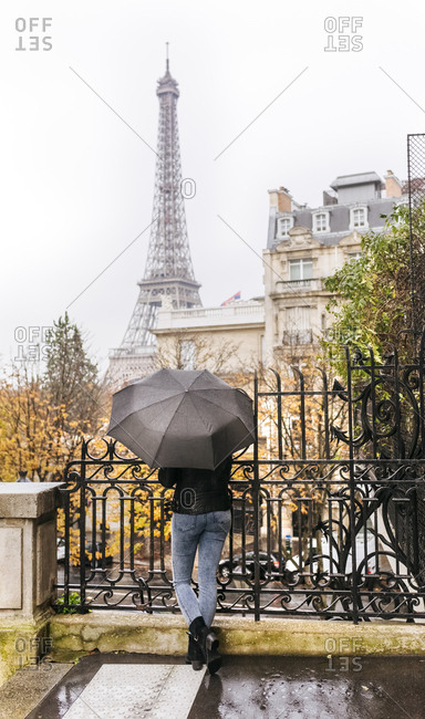 France- Paris- woman under umbrella with the Eiffel Tower in the background