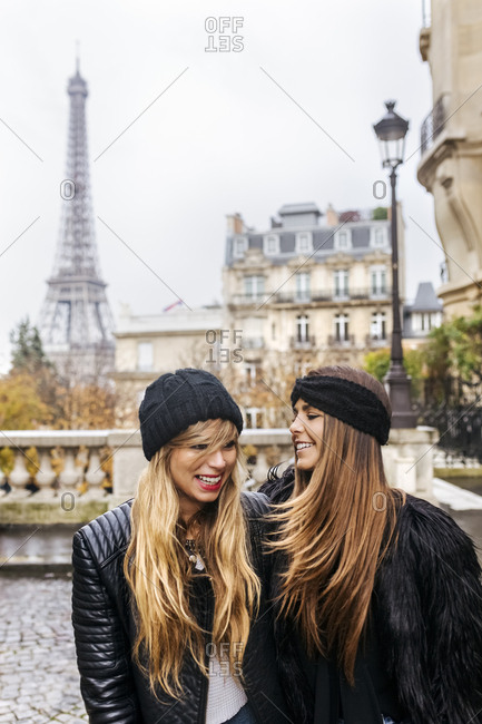 France- Paris- two best friends walking down the street with the Eiffel Tower in the background