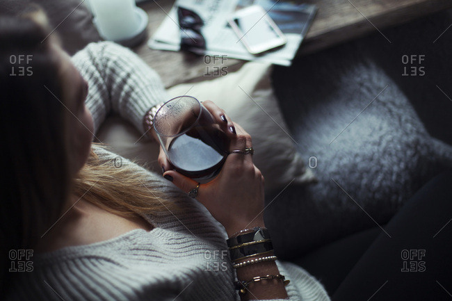 Young woman with glass of coffee relaxing on couch at home