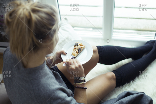 Young woman relaxing on sheepskin at home eating piece of cake