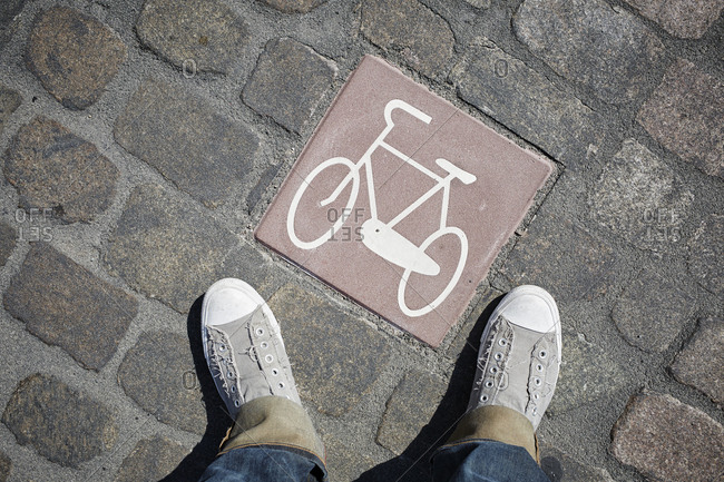 Person standing next to pictogram with bicycle on cobblestone pavement