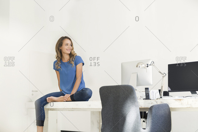 Casual businesswoman in office- sitting on desk- looking confident