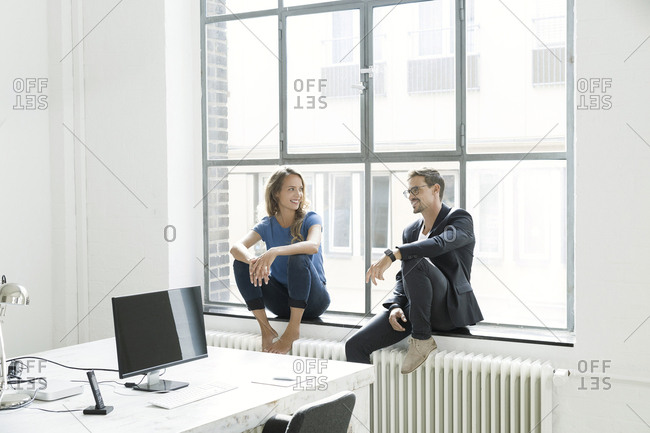 Colleagues sitting on window sill- talking