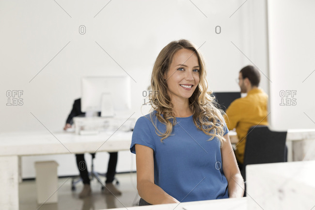 Casual businesswoman sitting in office- colleagues working in background