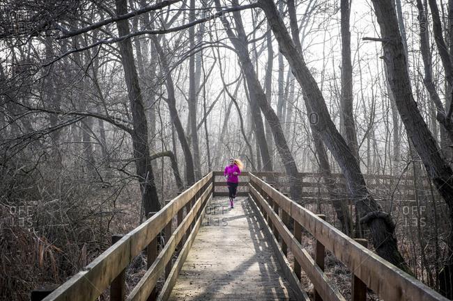 Woman running on wooden bridge through forest