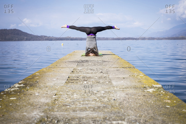 Woman practicing yoga doing a headstand on a pier at a lake
