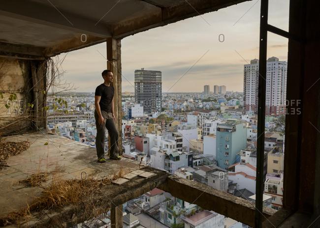 Vietnam- Ho Chi Minh City- man standing in ruin of a skyscraper