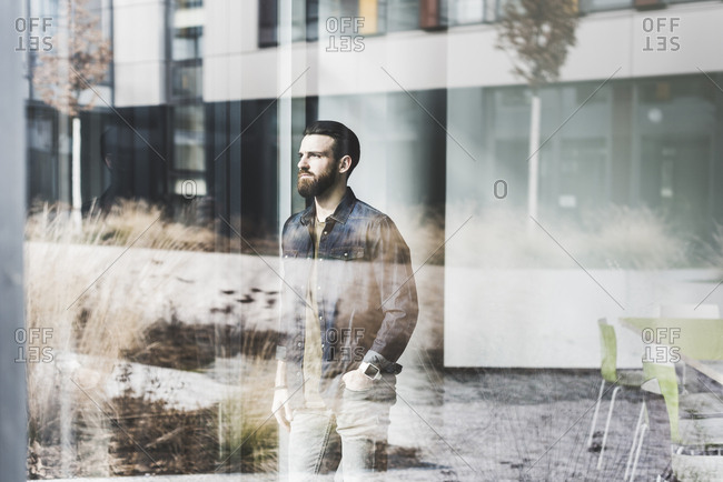 Young businessman standing at window pane- wearing smart watch