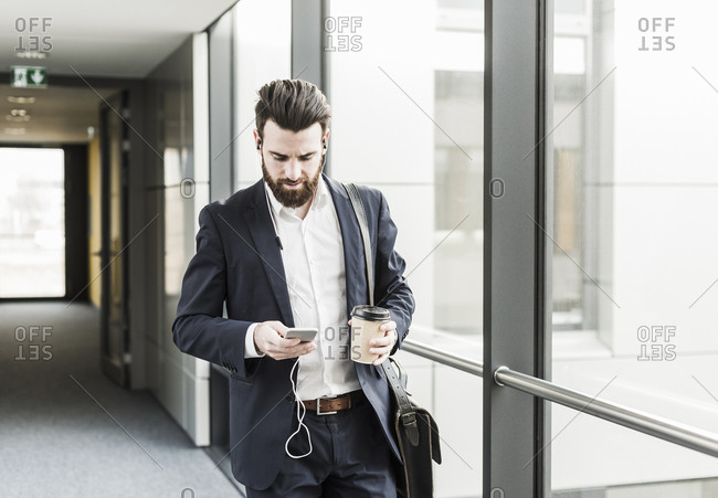 Businessman walking in office building while talking on the phone with ear phones