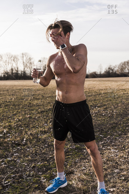 Bare-chested athlete in rural landscape pouring water over his face