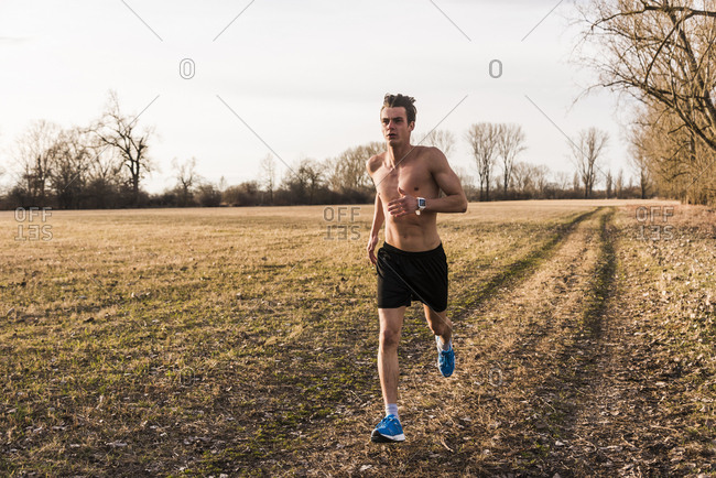Bare-chested man running in rural landscape
