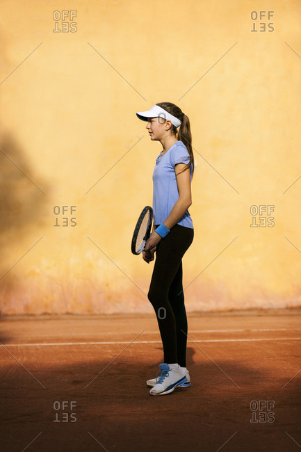 Teenage girl standing on tennis court