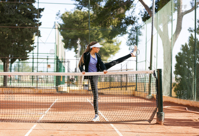 Teenage girl warming up on tennis court