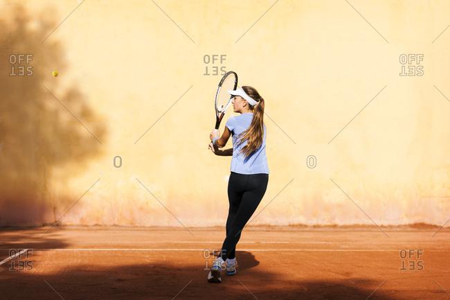Teenage girl playing tennis on court